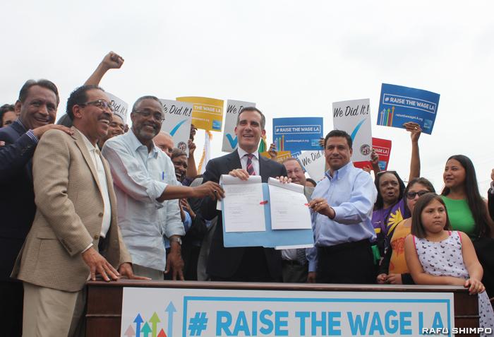 LA市で最低賃金の引き上げ案が1日に施行された。写真は同法案に署名した際のガーセッティー市長(中央)とLA市議や同法案支持者