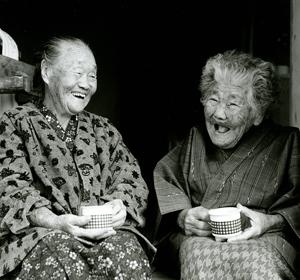 お茶を飲みながら談笑する元気な竹富島の老婆