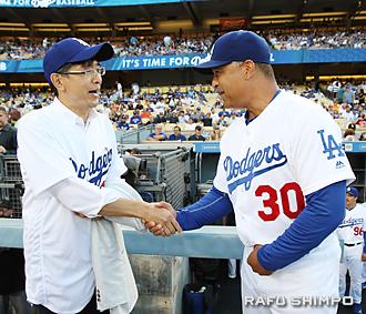試合開始直前に沖縄生まれのハーフ日本人デーブ・ロバーツ監督(右)を激励する千葉総領事