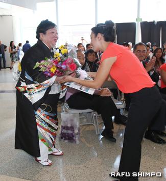 二世週祭ファースト・プリンセスのベロニカ・オオタさん(右)から花束を贈られる花柳禄福美師