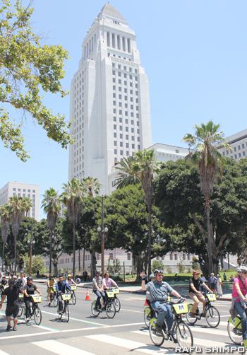 レンタル自転車に乗って市庁舎前を走行する市民