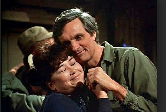 "Kellye Nakahara Wallett as Nurse Kellye and Alan Alda as Hawkeye Pierce in a scene from ""M*A*S*H."""