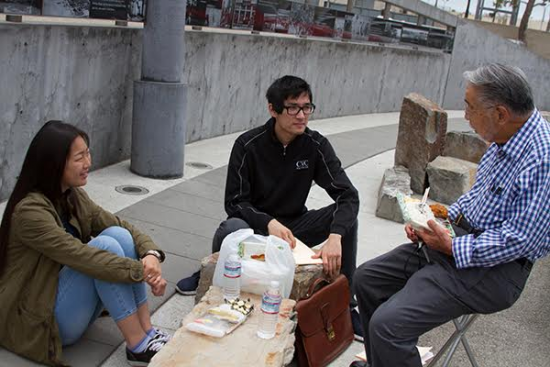 Minoru Tonai chats with Tuna Canyon Detention Center college interns Ariel Imamoto and Keith Matsushita at the Terminal Island Japanese Memorial. (Photo by Nancy Hayata)
