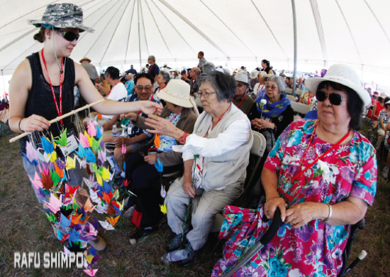 Andrea Ikeda volunteer passes out hand folded paper cranes to the attendees to be offered at the end of the memorial service. (MARIO G. REYES/Rafu Shimpo)