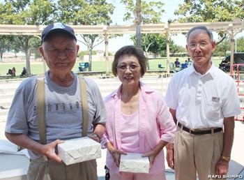80歳を迎え牧会長(右から)記念品を贈呈された平賀あきこさんと武良秀雄さん