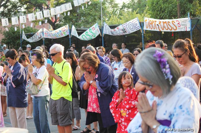 万灯会法要で先祖に祈りを捧げる参加者たち