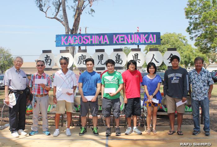鹿児島ファンデーションの山口弘会長(左端)から祝金を受け取った同会メンバーの高校卒業生と代理で出席したその家族ら