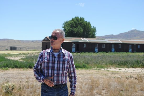 George Takei stands in front of the barrack at Heart Mountain.