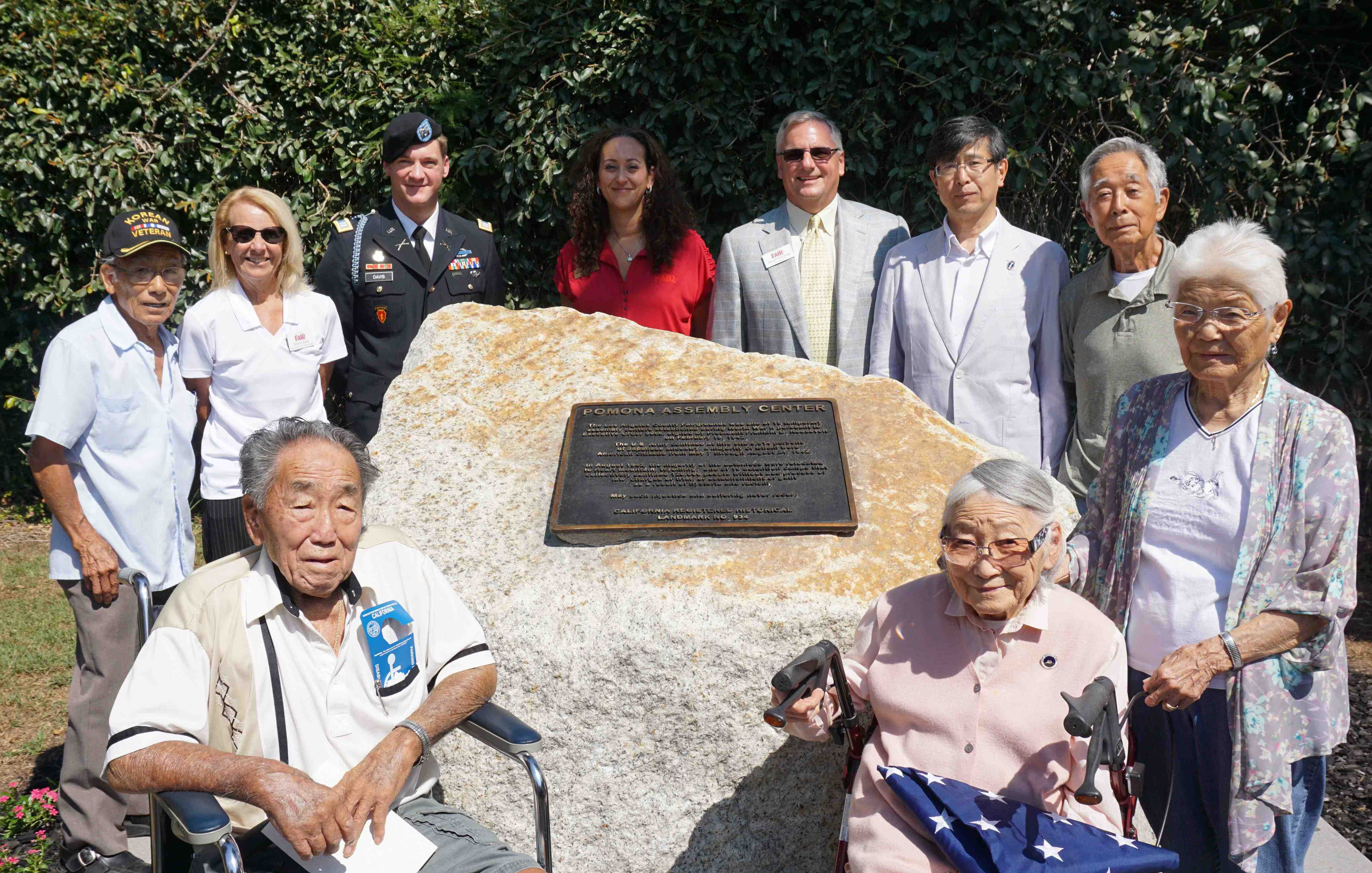 Dignitaries participating in the dedication were (from left) Bacon Sakatani, chair, Pomona Assembly Center Committee; Sharon Autry, communications/public relations, Fairplex; U.S. Army Capt. Joseph Davis, commander, SGV Recruiting Company; Tina Loza, director, Los Angeles County Fair Association; Dwight Richards, vice president of operations, Fairplex; and Consul General Akira Chiba, Consulate General of Japan in Los Angeles. Representing the older seniors in attendance were Ted Hashimoto, 94, and Yoshi Komaki, 95, in the back; Toshi Asano, 93, and Helen Munekiyo, 96, seated. (Photo by Patti Hirahara)