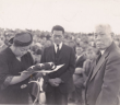 """Tom Ikeda's grandparents Fred Suyekichi and Akino Kinoshita (left and center) receive a flag in honor of their son Staff Sergeant Francis """"Bako"""" Kinoshita, killed in action in World War II, accompanied by a family friend. (Photo courtesy Tom Ikeda)"""