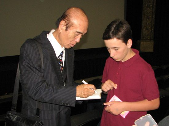"Masashiro Sasaki, Sadako's brother, gives his autograph to Cameron McIntyre, a young actor who appears in ""Orizuru 2015."" (J.K. YAMAMOTO/Rafu Shimpo)"
