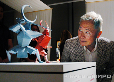 "George Takei examines two of the origami character figures used in ""Kubo,"" during an event last Thursday at JANM. Takei donated the figure of his character, Hosato, to the museum's collection. (MIKEY HIRANO CULROSS/Rafu Shimpo)."