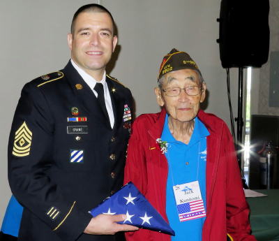 Jack Kunitomi, the oldest attendee at the Heart Mountain reunion, receives an American flag from U.S. Army First Sergeant Jeffrey Crane of the San Gabriel Valley Recruiting Company.