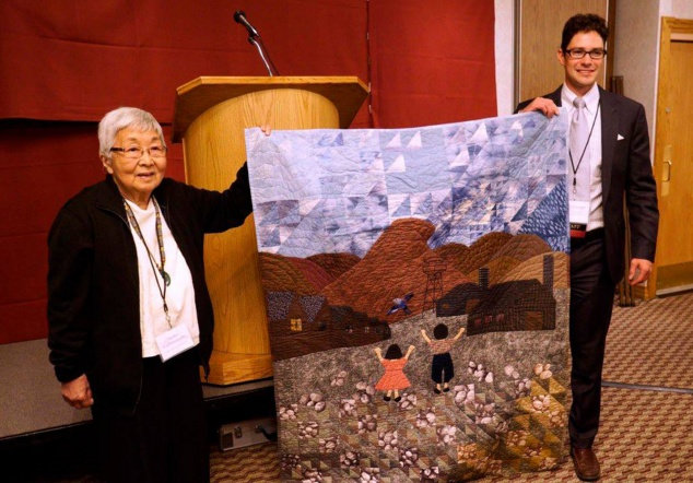 """Naoko Ito holds up her quilt, """"Letting Go,"""" with Heart Mountain Wyoming Foundation Executive Director Brian Liesinger during last year's Heart Mountain Pilgrimage."""