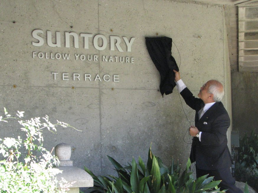 JACCC staff member Chester Ikei unveils the Suntory Terrace sign.