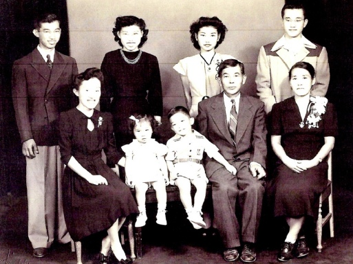 Family reunion after World War II, taken by Toyo Miyatake Studio in 1946. Back row, from left: Hiroshi, Kazumi, Kimiye, Yoshito. Front row, from left: Emiko, MeriJane, Kiyoshi, Papa, Mama. (Photo courtesy of Yosh Kuromiya)