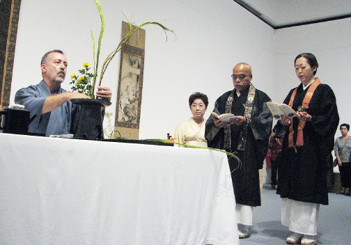 Rev. Nobuko Miyoshi and Rinban William Briones chant and attendant Izumi Minamitani watches as Jose Secido of the Ikenobo School creates an ikebana arrangement.