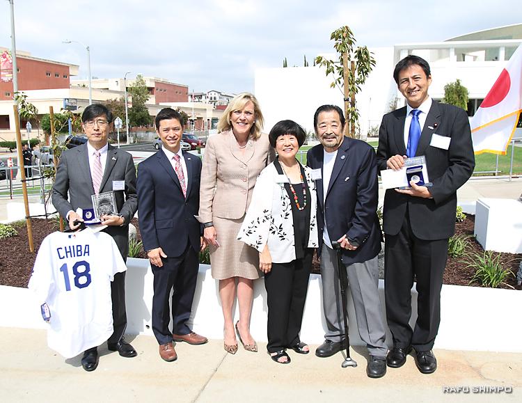 奉納した桜の木を背に、記念写真に納まる(右から)武井俊輔・外務大臣政務官、ゲイリー、リンダ・ヤマウチ市議ら。ヤマウチ市議からは、千葉明総領事(左端)にドジャースのレプリカジャージーが贈られた