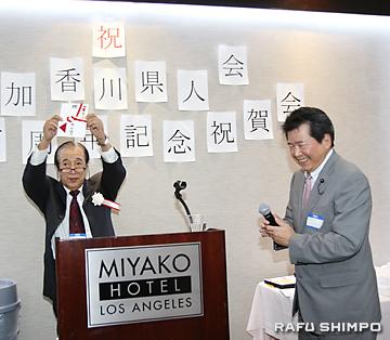 高田県議会副議長(右)から贈られた100周年記念の祝い金を披露する國宗会長