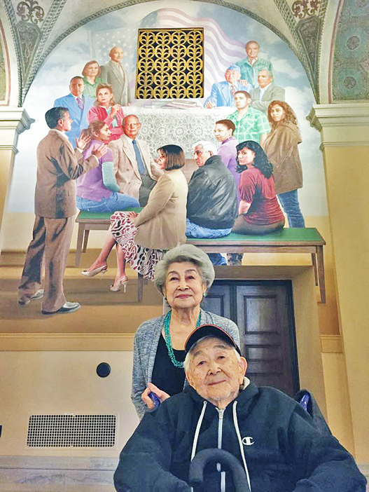 "George Yamaguchi and his wife Florence pose in front of the mural ""We the People, Out of Many, One"" at Bob Hope Patriotic Hall in April 2016. A rendering of George can be seen in the upper right corner, with Hope's hand on his shoulder Veteran and actor John Fujioka is depicted in the upper left part of the work. (Photos courtesy Georgiana Yoshioka)"