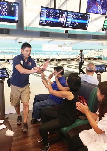 スペアを取り、チームメートに祝福される佐賀県人会会長の飯盛裕介さん(左)