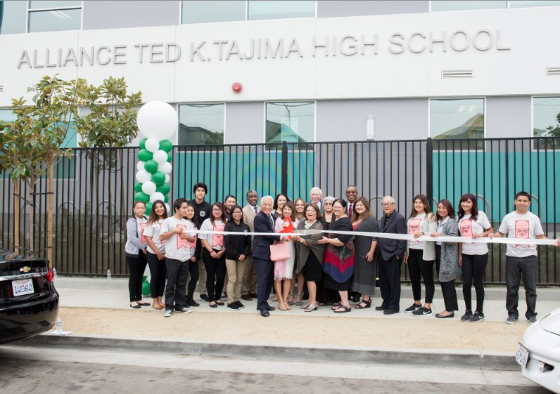 A ribbon-cutting was held Oct. 12 at Alliance Ted K. Tajima High School. Among those taking part were (holding scissors) Dale and Ayako Okuno, who were initiators of the naming honor, and Pam Tajima Praeger; Linda Tajima (wearing dark glasses), Wendy Tajima, Elaine Tajima, and Bill Ouchi. Dale Okuno and Ouchi are board members of Alliance College-Ready High Schools.