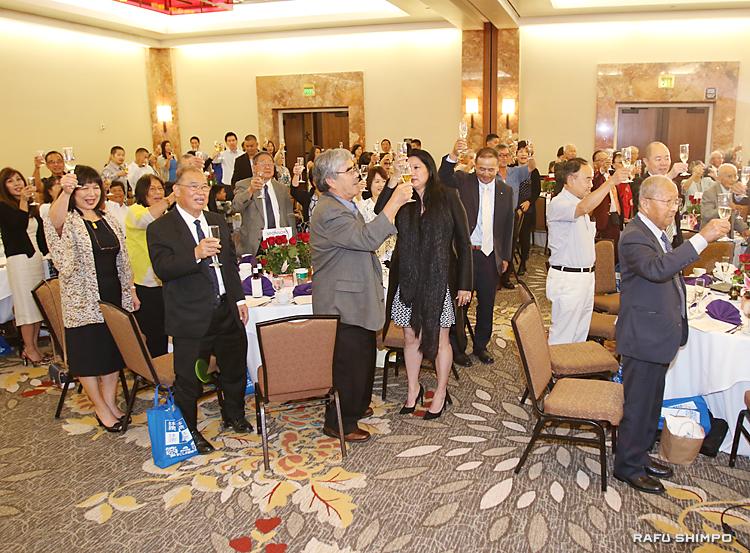 鹿児島県からの移住60周年を祝い乾杯する参加者。前列右端が西屋委員長、左端はマーガレット宮内・副委員長