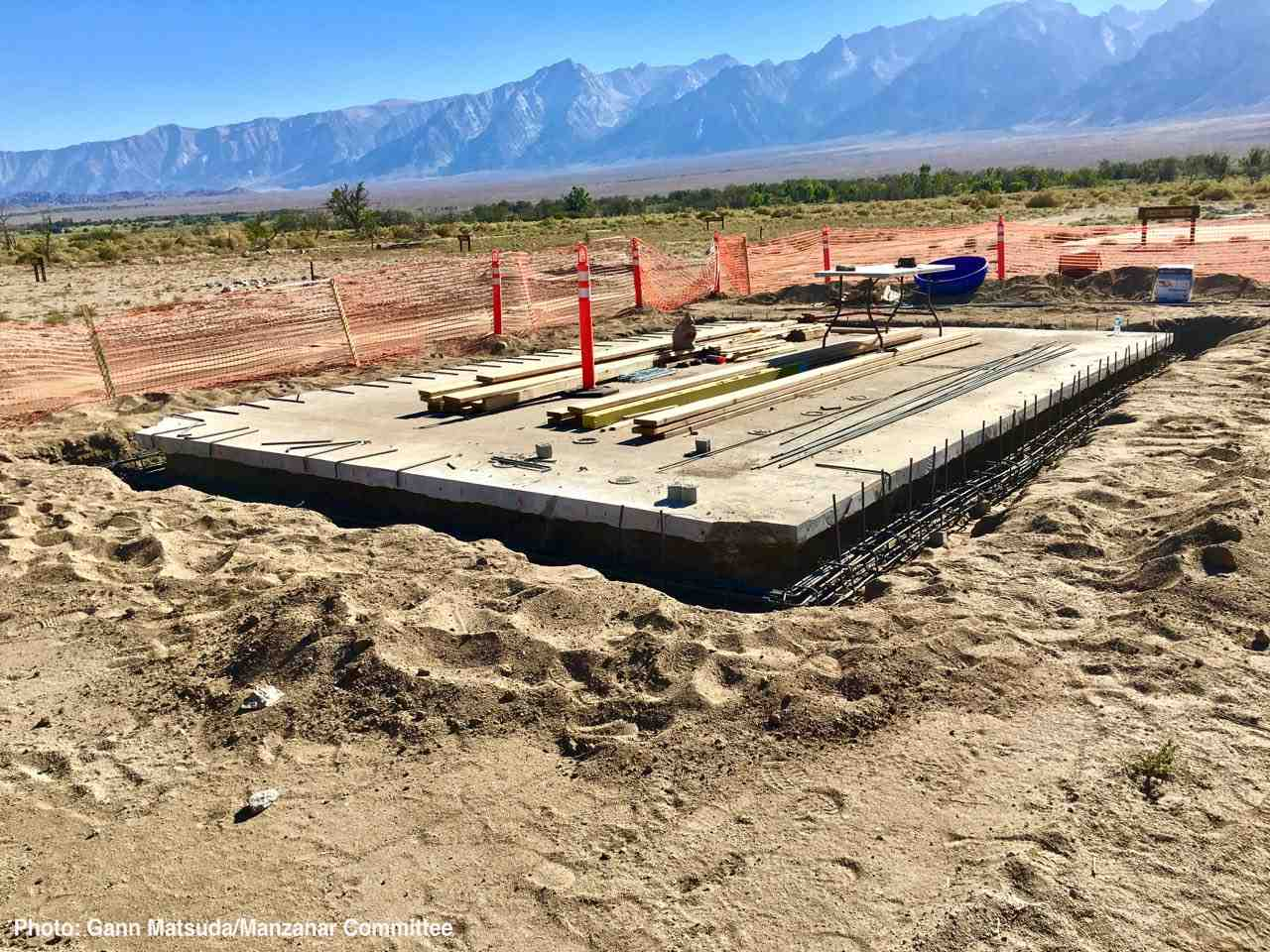Initial work on constructing a historic replica of the Block 14 women's latrine at Manzanar National Historic Site has begun. In this photo, the historic concrete slab foundation is being reinforced with rebar to meet current seismic standards. (Photo by Gann Matsuda/Manzanar Committee)