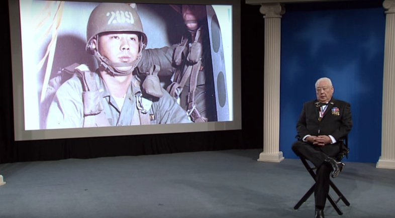 Vince Okamoto speaks as a photo of him from the Vietnam War is projected.