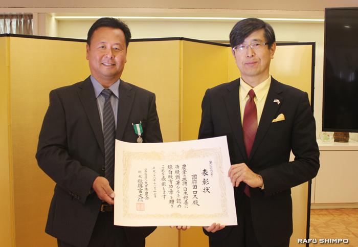 千葉明総領事(右)から表彰状が手渡された国府田ロス氏