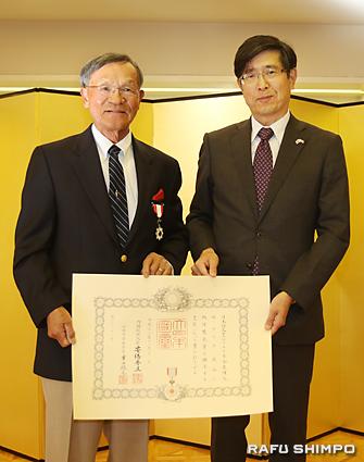 伝達式で千葉総領事(右)から「旭日双光章」を授与されるタック西さん