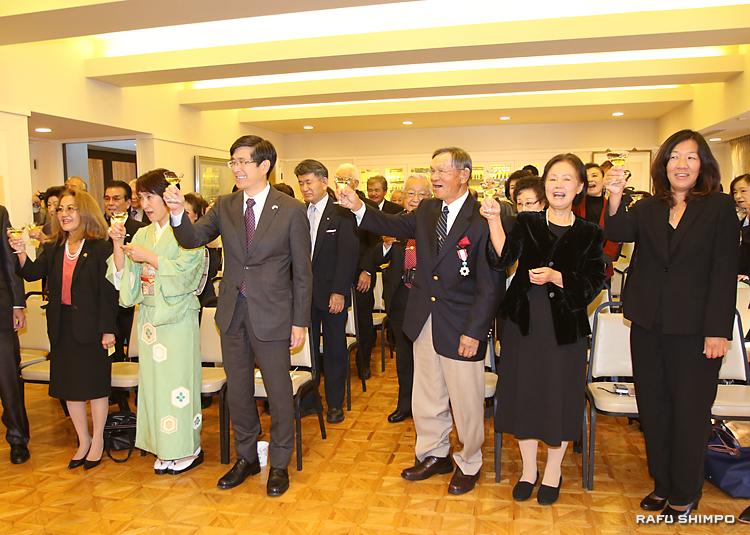 約40人の奉仕仲間と受章の喜びを分かち合い、祝杯を挙げる西さん(右から3人目)。右隣が敬子夫人