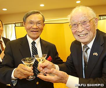 乾杯の音頭を取った三宅さん(右)から祝福を受ける西さん