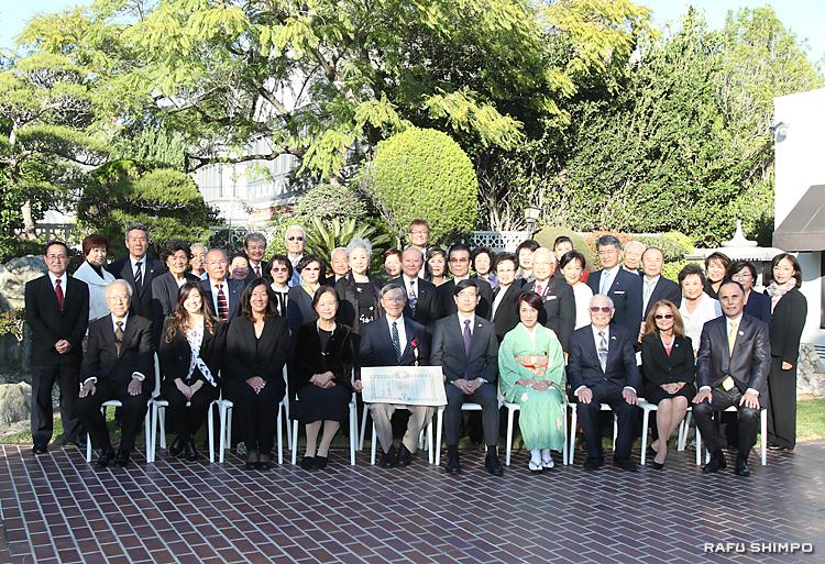 叙勲伝達式に招待された参加者と集合写真に納まる西さん(前列左から5人目)